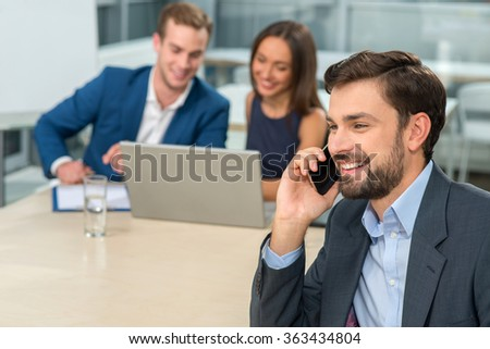 Attractive three business colleagues are taking part in a conference. They are sitting at the desk and smiling. The businessman is talking on the mobile phone. The man and woman are using laptop - stock photo