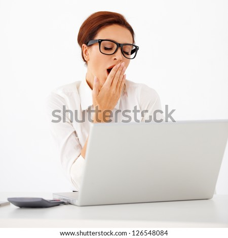 Attractive tired young businesswoman wearing glasses yawning with her hand to her mouth as she sits at her desk with a laptop - stock photo