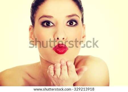 Attractive topless woman with dark make up blowing a kiss. - stock photo