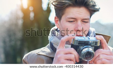 Attractive Tourist taking a photograph with vintage camera of Historic old village / town at sunset - Analog instagram style film emulation - stock photo