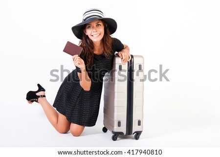 Attractive tourist woman showing passport with suitcase on isolated white background - travel and vacation concept - stock photo