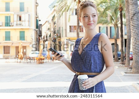 Attractive tourist woman standing in a Mediterranean destination city square holding and using smartphone technology to network while on a summer holiday, outdoors. Travel and technology. - stock photo