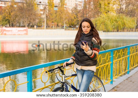 Attractive trendy casual young woman checking her mobile phone as she stands holding her bicycle on a walkway above a lake - stock photo