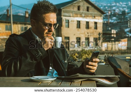 attractive trendy male model drinking coffee and looking in phone outdoors - stock photo