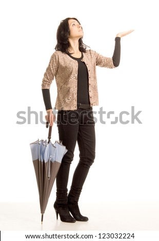 Attractive trendy woman worried about the rain holding out her hand and looking up at the sky while holding a closed umbrella in the other hand, full length studio portrait isolated on white - stock photo