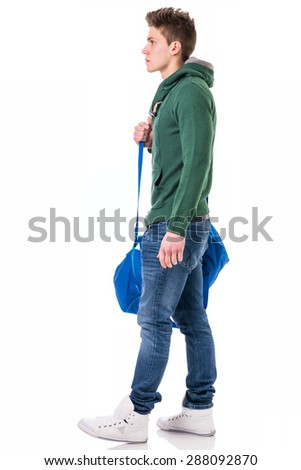 Attractive trendy young man with bag on shoulder strap, isolated on white background, walking to left - stock photo