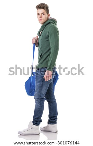 Attractive trendy young man with bag on shoulder strap, isolated on white background, walking to left, looking at camera - stock photo