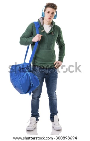 Attractive trendy young man with bag on shoulder strap, listening to music with headphones, isolated on white background, looking at camera - stock photo