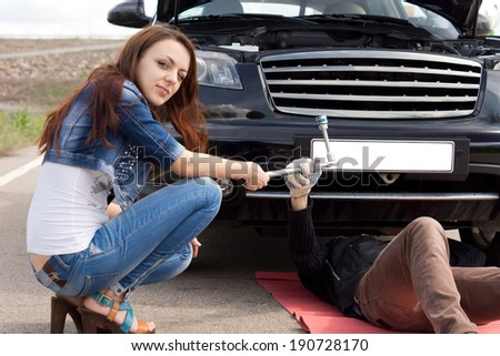 Attractive trendy young woman fixing her car helping the mechanic who responded to her call for roadside assistance following a breakdown by handing him a socket spanner - stock photo