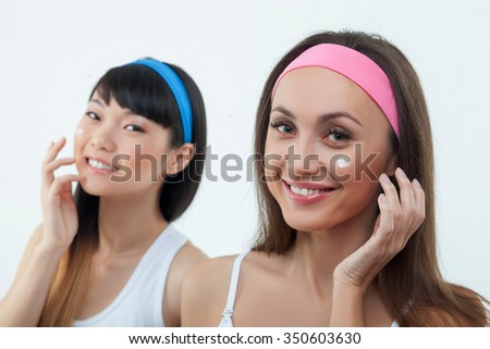 Attractive two asian and caucasian girls are applying cream on cheek. They are smiling and looking at camera with joy. Isolated on background - stock photo