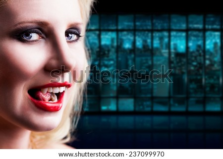 attractive vampire licking her teeth - stock photo