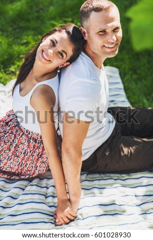 Attractive vertical top view of a beautiful cute couple in love sitting on a picnic blanket. Caucasian happy man and smiling brunette woman looking up, sitting on stripes plaid on green grass.