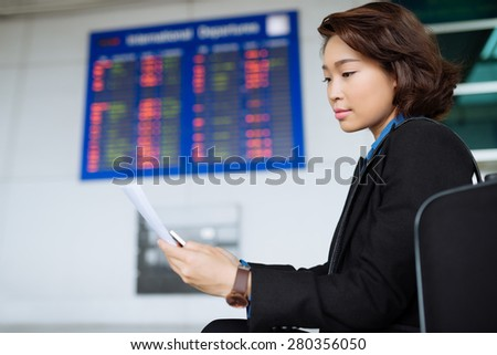 Attractive Vietnamese business lady reading document at the airport - stock photo
