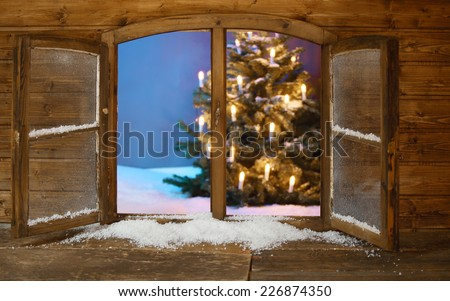 Attractive View of Lighted Christmas Tree on Snow from Vintage Wooden Window Pane During Holidays. - stock photo