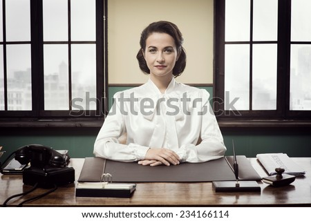 Attractive vintage business woman sitting at office desk and smiling at camera - stock photo