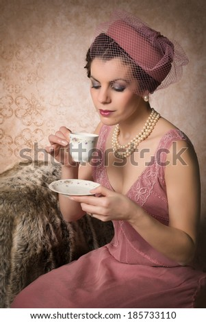 Attractive vintage 1920s lady with flapper dress and matching hat drinking tea - stock photo