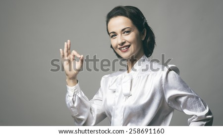 Attractive vintage woman giving ok sign and smiling - stock photo