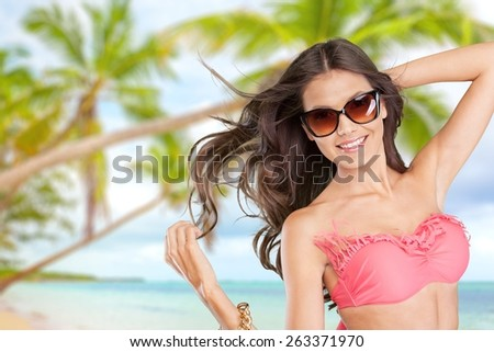 Attractive. Vivacious sexy young brunette woman with a beautiful smile and her hair blowing in the breeze posing in a white bikini  three quarter isolated studio portrait - stock photo