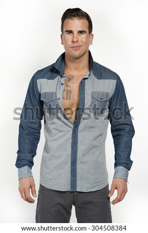 Attractive white caucasian male model smirking wearing a jean shirt posing in a studio on a white background while looking at the camera. - stock photo