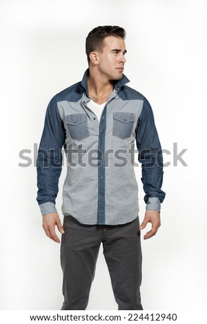 Attractive white caucasian male model wearing a jean shirt and gray pants posing in a studio on a white background while looking away from the camera. - stock photo