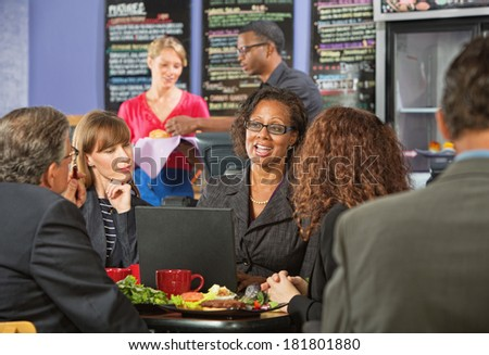 Attractive white collar workers meeting for a working lunch - stock photo