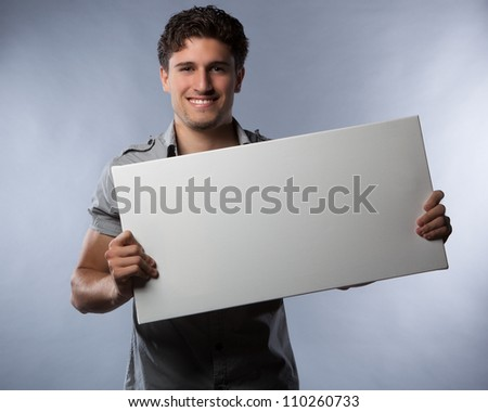 Attractive white guy holding object in studio against grey background wearing a grey shirt.