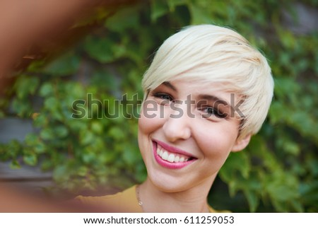Attractive white woman taking a selfie against an ivy fence backdrop