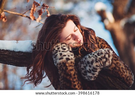 Attractive woman admiring nature and enjoying winter sunlight. She is carefree, happy and serene. The sunny winter day, so the woman in the warm clothing.  - stock photo