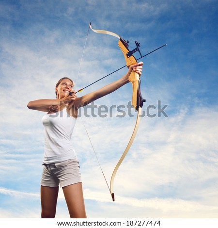 Attractive woman aiming with bow and arrow with blue sky on background. - stock photo