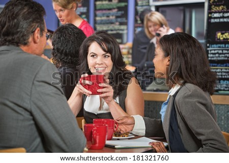 Attractive woman and coworkers with coffee cups in restaurant - stock photo