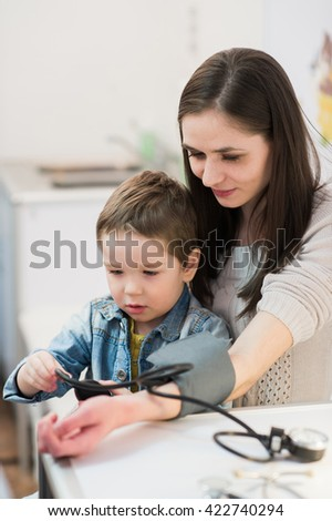 Attractive woman and her kid with a blood pressure meter tonometer