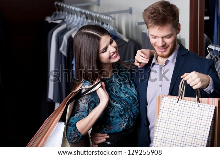 Attractive woman and young man go shopping at the store - stock photo