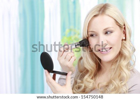 Attractive woman applies cosmetic powder on her face