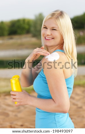 Attractive woman applies sun lotion