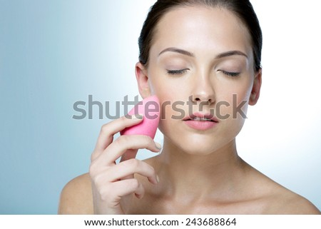 Attractive woman applying foundation by sponge on face for make-up - stock photo