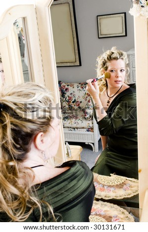 attractive woman applying makeup in front of beauty salon mirror