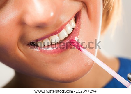 Attractive woman applying makeup on her face - stock photo