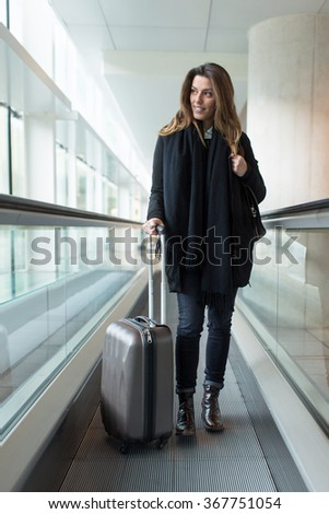 Attractive woman arriving at the airport in winter - stock photo