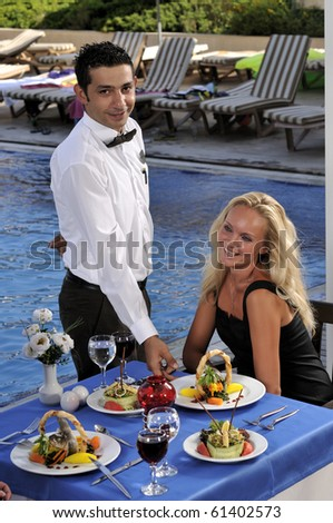Attractive woman at a restaurat having dinner being served by a waiter - a series of RESTAURANT images. - stock photo