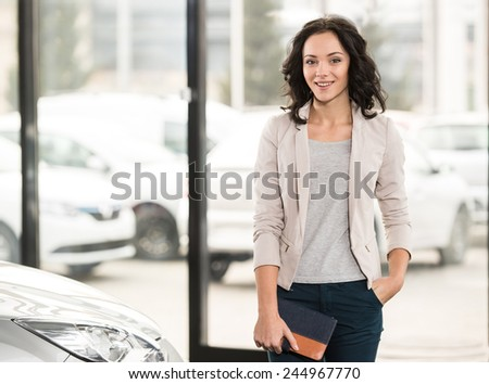 Attractive woman at car salon is choosing a car. Looking at the camera. - stock photo