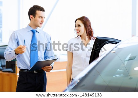 Attractive woman at car salon with consultant choosing a car - stock photo