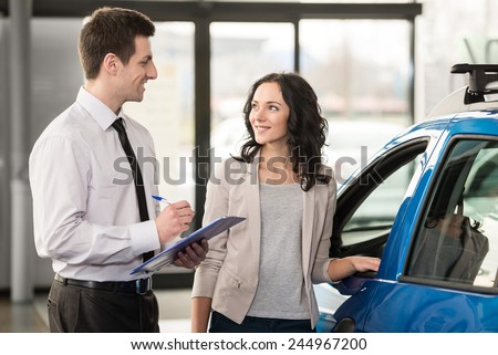 Attractive woman at car salon with consultant choosing a car. - stock photo