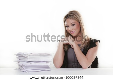 attractive woman at her desk looking happy in her work with a lot of paper work to do - stock photo