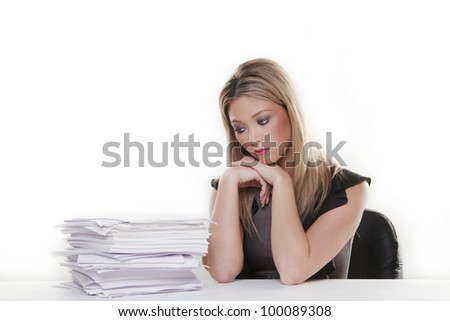 attractive woman at her desk with a lot of paper work to do - stock photo