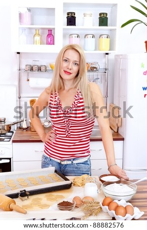 Attractive woman baking cake in the kitchen - stock photo