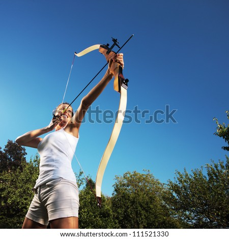 Attractive woman bending a bow and aiming in the sky - stock photo