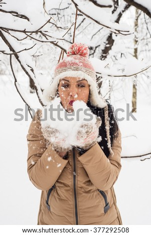 Attractive woman blowing snow flakes in front of camera in park - stock photo