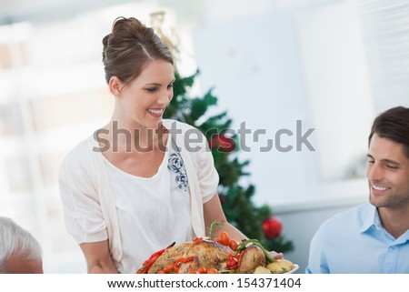 Attractive woman bringing a roast chicken at table for christmas dinner - stock photo