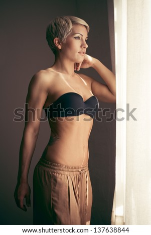 attractive woman by a window - stock photo