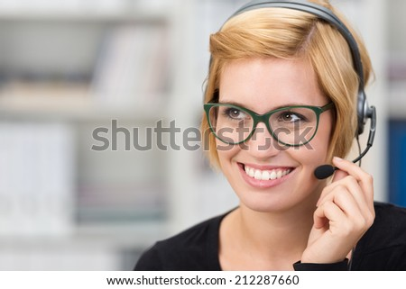 Attractive woman call centre operator wearing heavy framed glasses and a headset smiling as she listens to a conversation with a customer - stock photo